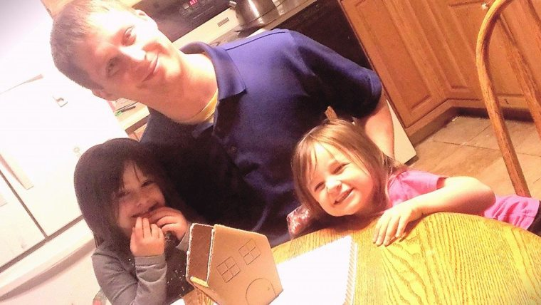 Ben doin work on the ginger bread house with the girls